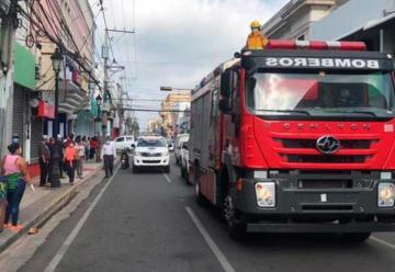Bomberos distancian a las personas echándole agua desde un camión
